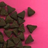 Comida para gatos en fondo rosado Imagenes de archivo