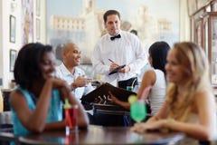 Comida que ordena de la gente al camarero en restaurante Fotos de archivo
