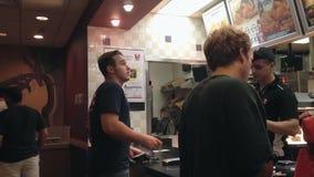 Comida que ordena de la gente dentro de la tienda de KFC Imagenes de archivo