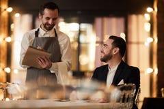 Comida que ordena de la huésped en restaurante imagen de archivo libre de regalías