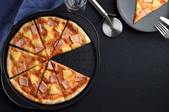 Comida rápida hecha en casa: pizza cortada con la piña y el jamón en fondo oscuro Imagenes de archivo
