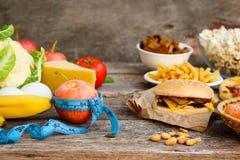 Comida rápida y comida sana Concepto que elige la nutrición correcta o de la consumición de los desperdicios foto de archivo libre de regalías