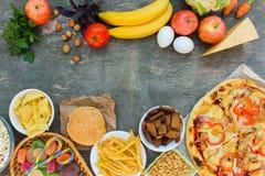 Comida rápida y comida sana en viejo fondo de madera foto de archivo