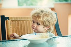 Comida sabrosa, niño lindo que come los espaguetis El niño en la cocina en la tabla que come las pastas Comida italiana para los  imagen de archivo libre de regalías