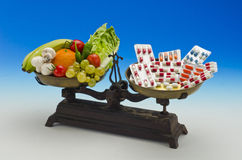 Comida sana contra píldoras médicas Foto de archivo libre de regalías