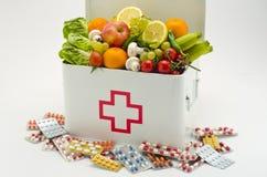 Comida sana contra píldoras médicas Fotografía de archivo