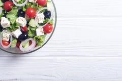 Comida sana de la ensalada griega de las verduras frescas en fondo de madera foto de archivo libre de regalías