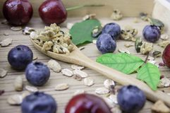 Comida sana de la mañana con el Granola y muesli en cuchara, bayas y cerezas de madera con las hojas verdes colocadas en madera h imagen de archivo
