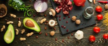 Comida sana del vegano que cocina los ingredientes Verduras puestas planas, frutas, aguacates, nueces, setas, cebollas, habas ver imagen de archivo