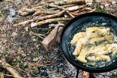 Comida sana en acampar: los pescados fryed en el wok negro critican al aire libre Imagen de archivo libre de regalías
