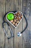 Comida sana en corazón y concepto de la dieta del colesterol en fondo de madera foto de archivo