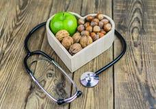 Comida sana en corazón y concepto de la dieta del colesterol en fondo de madera imagen de archivo