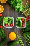 Comida sana en envases Ensalada con el tomate, pepino, anaranjado en envases en la opinión superior del fondo de madera Foto de archivo