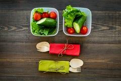 Comida sana en envases Ensalada con el tomate y el pepino en envases en la opinión superior del fondo de madera Foto de archivo libre de regalías