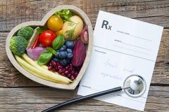 Comida sana en estetoscopio del corazón y dieta de la prescripción y concepto médicos de la medicina imagenes de archivo