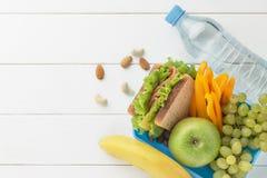 Comida sana fresca en fiambrera con el plátano y la botella de agua en la tabla de madera blanca Imagenes de archivo