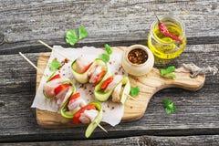 Comida sana: pinchos con el prendedero del pollo, calabacín, pimienta dulce roja, con aceite de oliva y sal en un de madera simpl foto de archivo libre de regalías