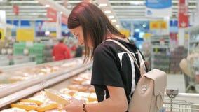 Comida sana que hace compras de la mujer joven en supermercado venta, compras, consumerismo y concepto de la gente almacen de metraje de vídeo