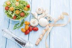 Comida sana Setas y ensalada frescas del arugula, tomates de cereza en fondo azul claro Comidas de la dieta imagen de archivo
