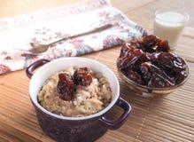 Comida sana simple Harina de avena con las fechas y la leche Imagen de archivo