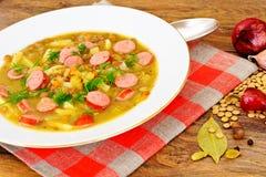 Comida sana y de la dieta: Sopa con las lentejas, el apio y la salchicha Fotografía de archivo