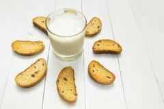 Comida sana, yogur amargo en una taza de cristal y galletas con las pasas en una tabla blanca imágenes de archivo libres de regalías