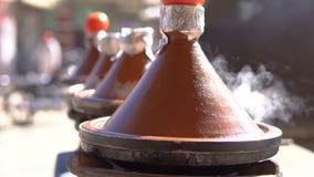 Comida tradicional de Tajine del marroquí que cocina en los potes de Tajine en el fuego con humo y los tomates en el top metrajes