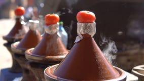 Comida tradicional de Tajine del marroquí que cocina en los potes de Tajine en el fuego con humo y los tomates en el top almacen de video
