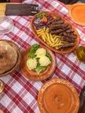 Comida tradicional del cevapi, de la mantequilla, y del pan de Montenegro en un mantel rojo de la tela escocesa y placas de cerám fotografía de archivo
