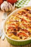 Comida vegetariana - cazuela de la patata con los tomates, el ajo y el queso Foto de archivo