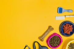 Comida y accesorios de perro en la opinión superior del fondo amarillo Imagen de archivo