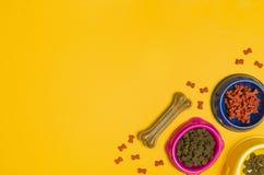 Comida y accesorios de perro en la opinión superior del fondo amarillo Foto de archivo