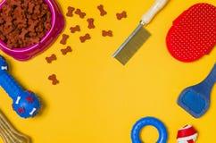 Comida y accesorios de perro en la opinión superior del fondo amarillo Imagenes de archivo
