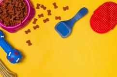 Comida y accesorios de perro en la opinión superior del fondo amarillo Fotos de archivo libres de regalías