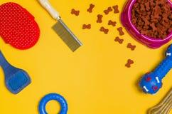 Comida y accesorios de perro en la opinión superior del fondo amarillo Fotografía de archivo libre de regalías