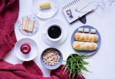Comida y café clasificados con el cuaderno en la tabla fotografía de archivo