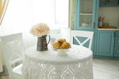 Comida y flores en una tabla de cocina por la mañana foto de archivo libre de regalías
