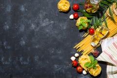 Comida y fondo italianos de los ingredientes con las verduras frescas, tomates, aceite de oliva, orégano, ajo, sal, pimienta, alb fotografía de archivo