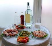 Comida y licor en la tabla servida fotografía de archivo
