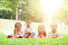 Comidas campestres asiáticas felices de los niños al aire libre imagenes de archivo