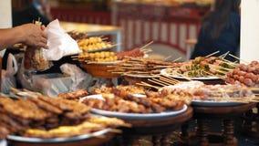 Comidas cocinadas calientes en el mercado de la comida de la calle El vendedor pone kebabs con las setas y el tocino en un bolso, almacen de video