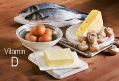 Comidas que contienen la vitamina D en una tabla de madera Imagen de archivo libre de regalías