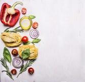 Comidas sanas, concepto vegetariano que cocina las pastas con la harina, verduras, aceite e hierbas, cebolla, pimienta en fondo r Fotografía de archivo libre de regalías