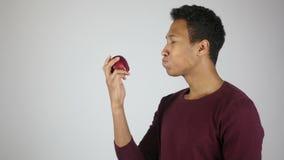 Comiendo Apple fresco rojo, masticando al hombre joven hambriento