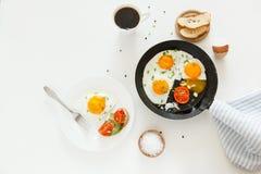 Comiendo en el proceso, los huevos fritos en un sartén y en una placa, la tostada con el aguacate y una taza de café para el desa Fotografía de archivo libre de regalías