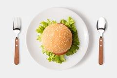 Comiendo la hamburguesa del Bbq en el plato aislado en el fondo blanco truncamiento foto de archivo