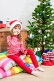 Comiendo a la muchacha de las galletas en la Navidad roja adornó la ropa que se sentaba en la almohada cerca de árbol verde con l Foto de archivo libre de regalías
