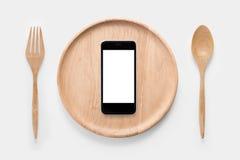 Comiendo smartphone en el sistema de bifurcación, de cuchara y de madera del plato aislada Foto de archivo libre de regalías
