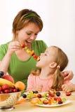 Comiendo un bocado sano - rebanadas de la fruta en el palillo Foto de archivo libre de regalías