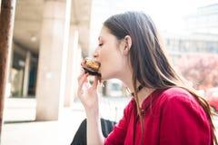 Comiendo una torta dulce deliciosa agradable adentro al aire libre Foto de archivo libre de regalías